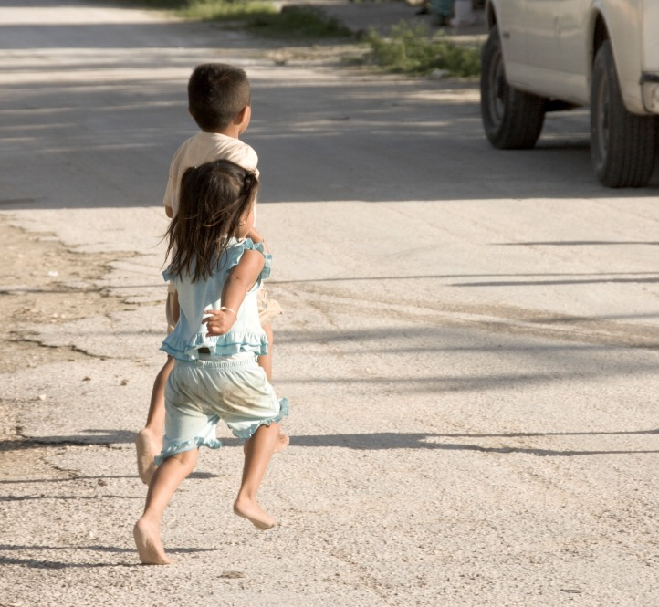 Bare feet children on street of Yucatan village running for tourists bus, Mexico