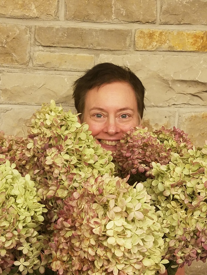 Katherine Engel smiles while hiding behind a rather large bouquet of flowers.