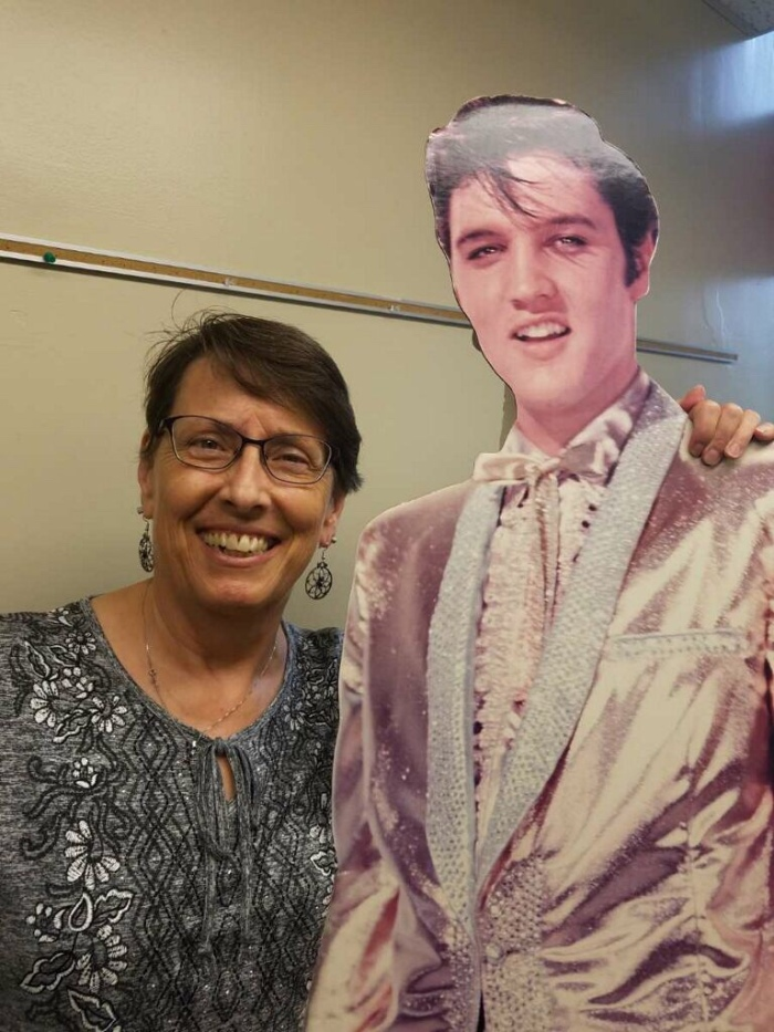 Sue Kmetz is standing next to a cardboard cut-out of Elvis. Elvis is rather flamboyantly dressed. Sue less so, but she still looks nice.