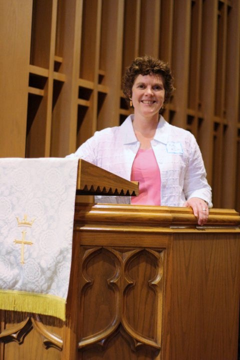 Kathy Itzen is smiling behind the pulpit. The pulpit has a white cloth banner with gold embroidery, which means this was likely taken at Easter time.